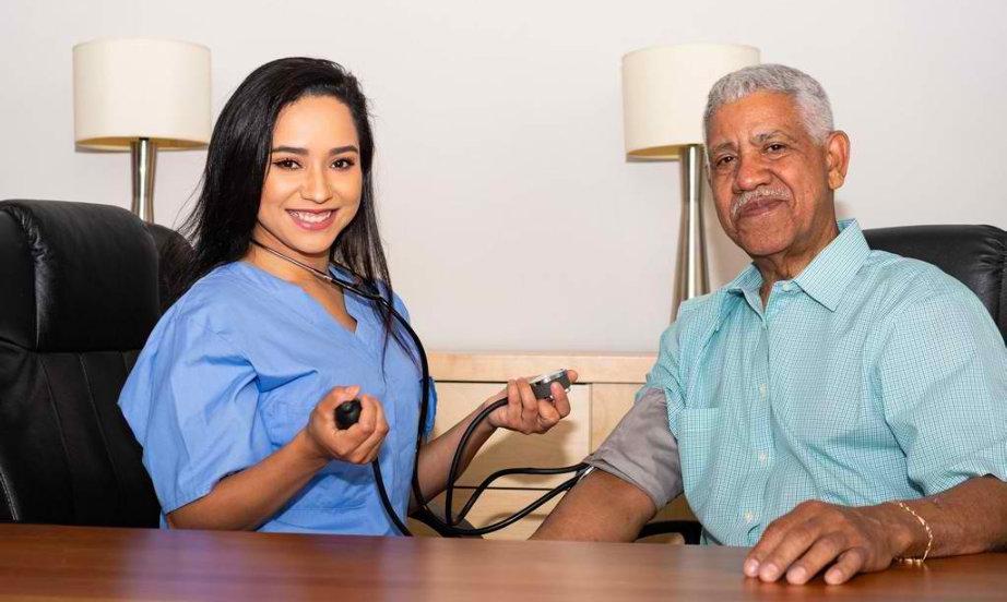 woman checking senior man's blood pressure