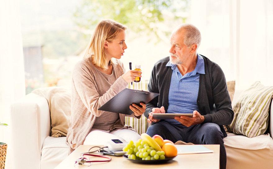 woman preparing medication for senior man