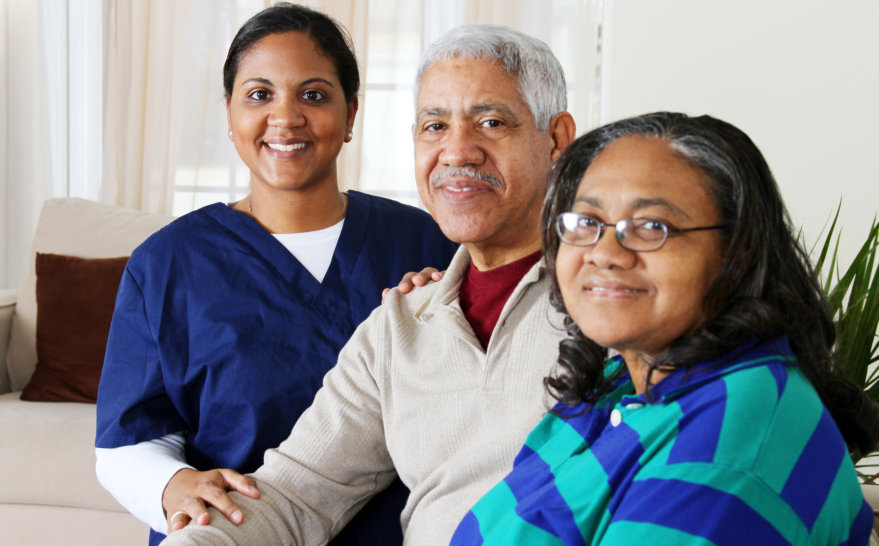 caregiver with senior man and woman smiling