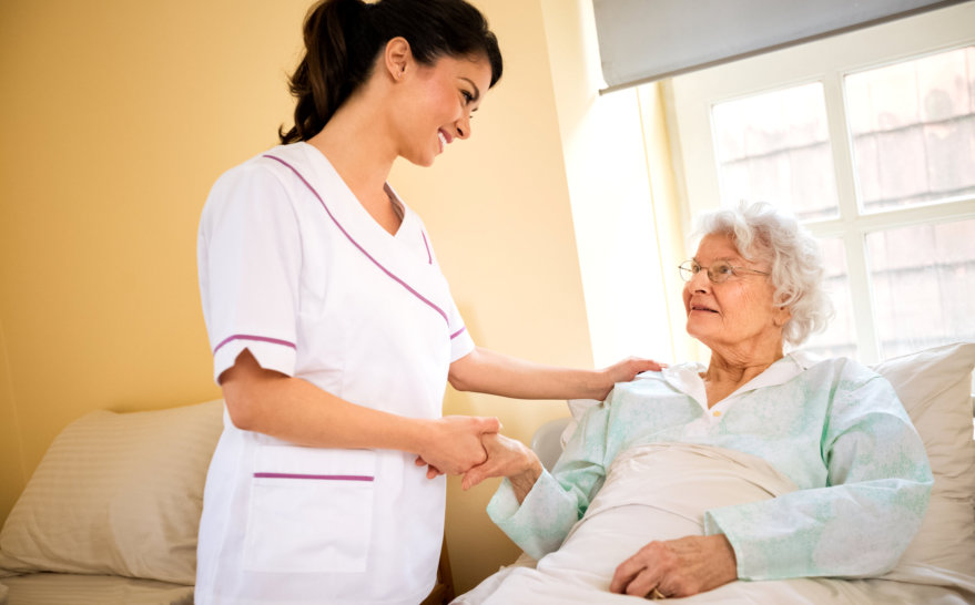 caregiver holding the hand of senior woman