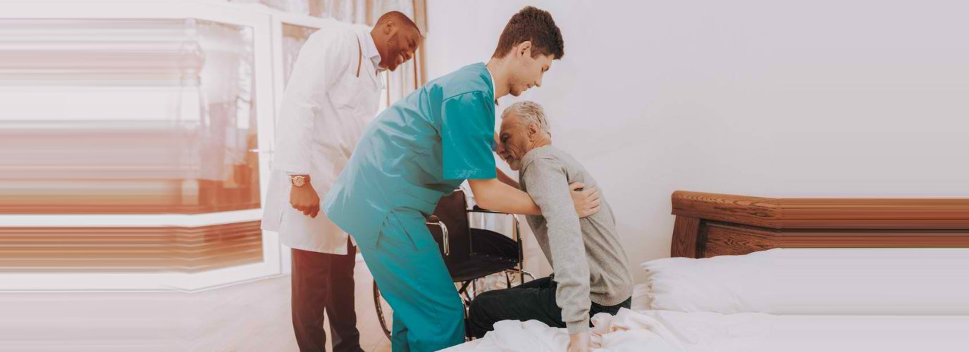 caregiver helping a man get up from bed
