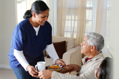 caregiver serving food to senior man and woman