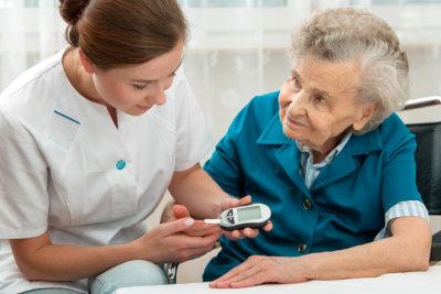 woman checking senior woman's sugar level