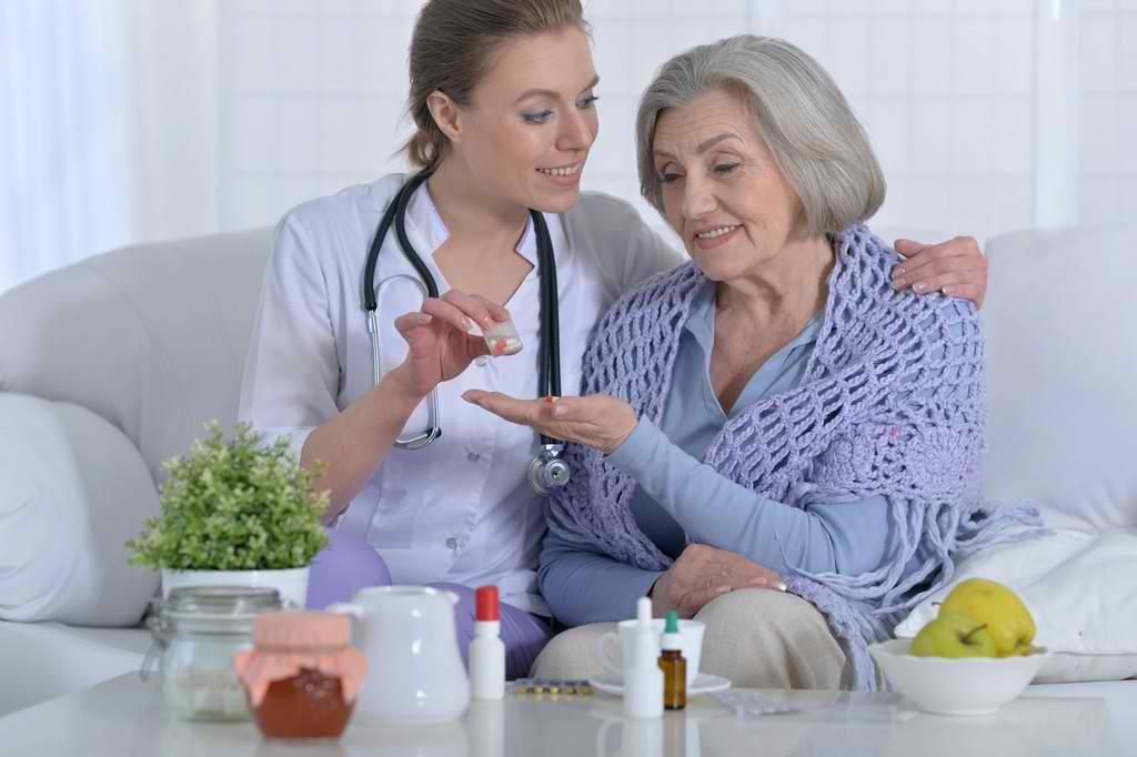 nurse giving medication to senior woman