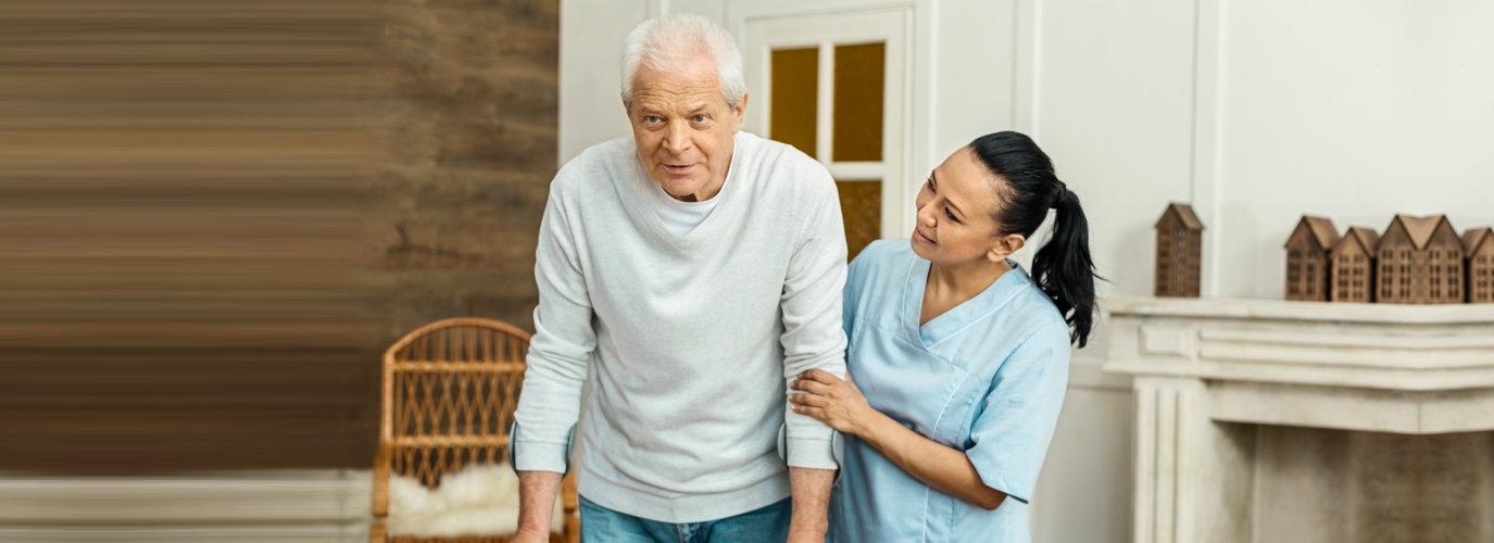 caregiver assisting a senior man